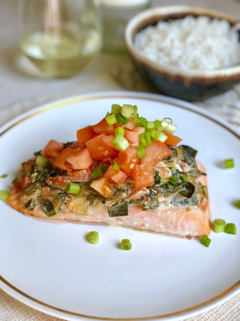Salmon on plate topped with spinach, leek and white wine sauce with fresh tomatoes and green onions